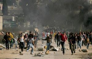 Jovens palestinos jogam pedras contra soldados israelenses perto de Tulkarem, na Cisjordânia, em janeiro de 2009 (Foto: Arquivo AFP)