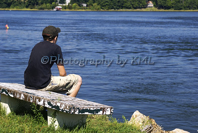 a young man on a bench beside the water