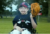 Zac posing in his wheel chair for his baseball team photo.