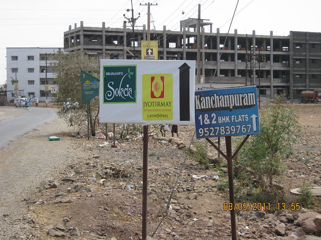 To Way Boards of Kanchanpuram, Solacia & Green Groves and under construction buildings of Moze College on the road to Karia Developers' Konark Meadows - 1 BHK 2 BHK 3 BHK Flats - at RMC Garden Compound - behind Moze College - Wagholi - Nagar Road - Pune