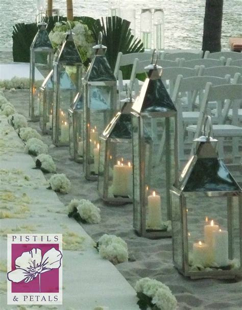 Silver Lanterns with Candles leading to beach Chuppah