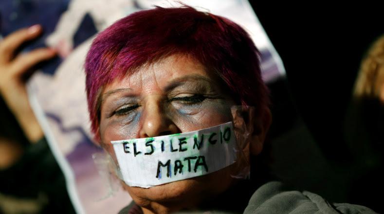 """La mujer tiene cinta que cubre su boca con las palabras """"El silencio mata"""" para no ocultar la violencia contra las mujeres."""