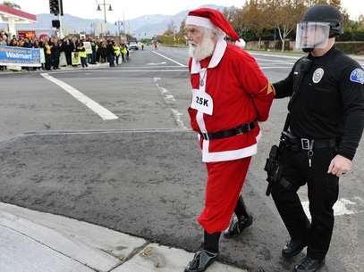 Homem vestido de Papai-Noel é preso durante protestos de funcionários do Wal-Mart Foto: AP