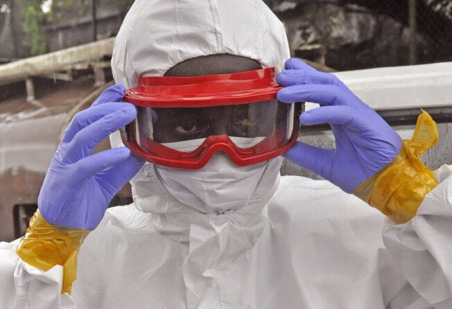 A Liberian health worker prepares his Ebola protective gear Friday, Aug. 29, 2014, in Monrovia, Liberia. The Ebola outbreak spreading through Guinea, Sierra Leone, Liberia and Nigeria has reportedly reached Senegal.