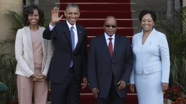 "President Barack Obama waves next to First Lady Michelle Obama, South Africa""s President Jacob Zuma and his wife, First Lady Thobeka Madiba-Zuma"