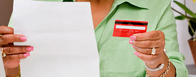 Woman with credit card bill. (Jupiterimages)