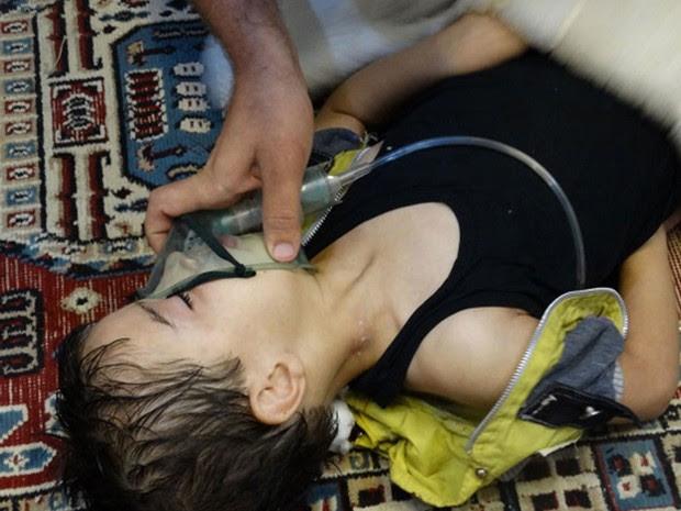 21/8 - Menino recebe cuidados e respira com a ajuda de uma máscara de oxigênio em Damasco após ataque de forças do governo (Foto: Maher al-Zaybaq/Shaam News Network/Reuters)