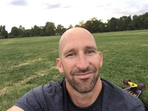 Tim Pahuta sitting in front of a field of grass