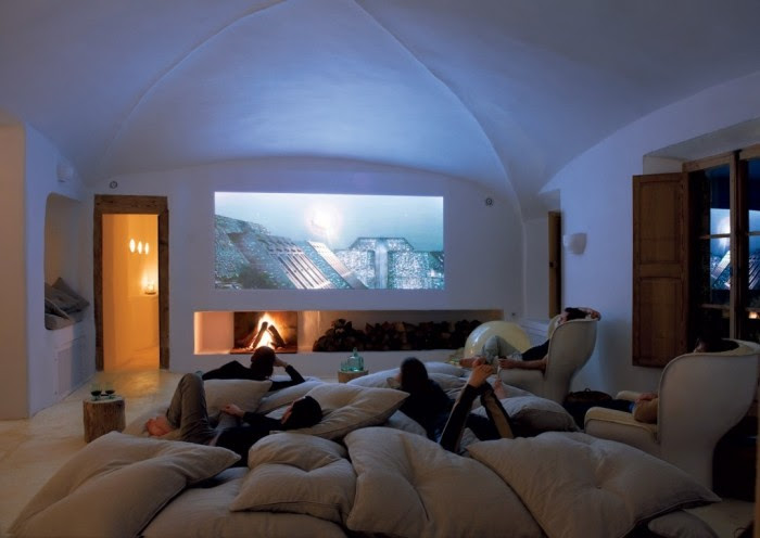 The dome-shaped ceiling opens up this media room basement . The fireplace under the media screen offers ambiance.