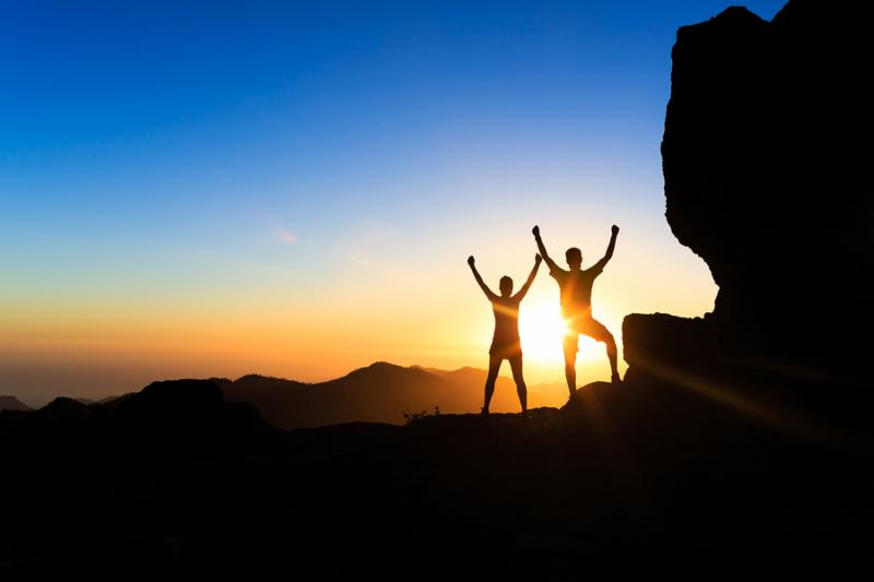 Teamwork couple hikers success in sunset mountains accomplish with arms up outstretched. Young man and woman on rocky mountain range looking at beautiful inspirational landscape view Gran Canaria Canary Islands.