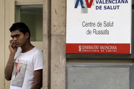 Un inmigrante habla por teléfono ante el centro de Salud de Ruzafa.   Juan Carlos Cárdenas