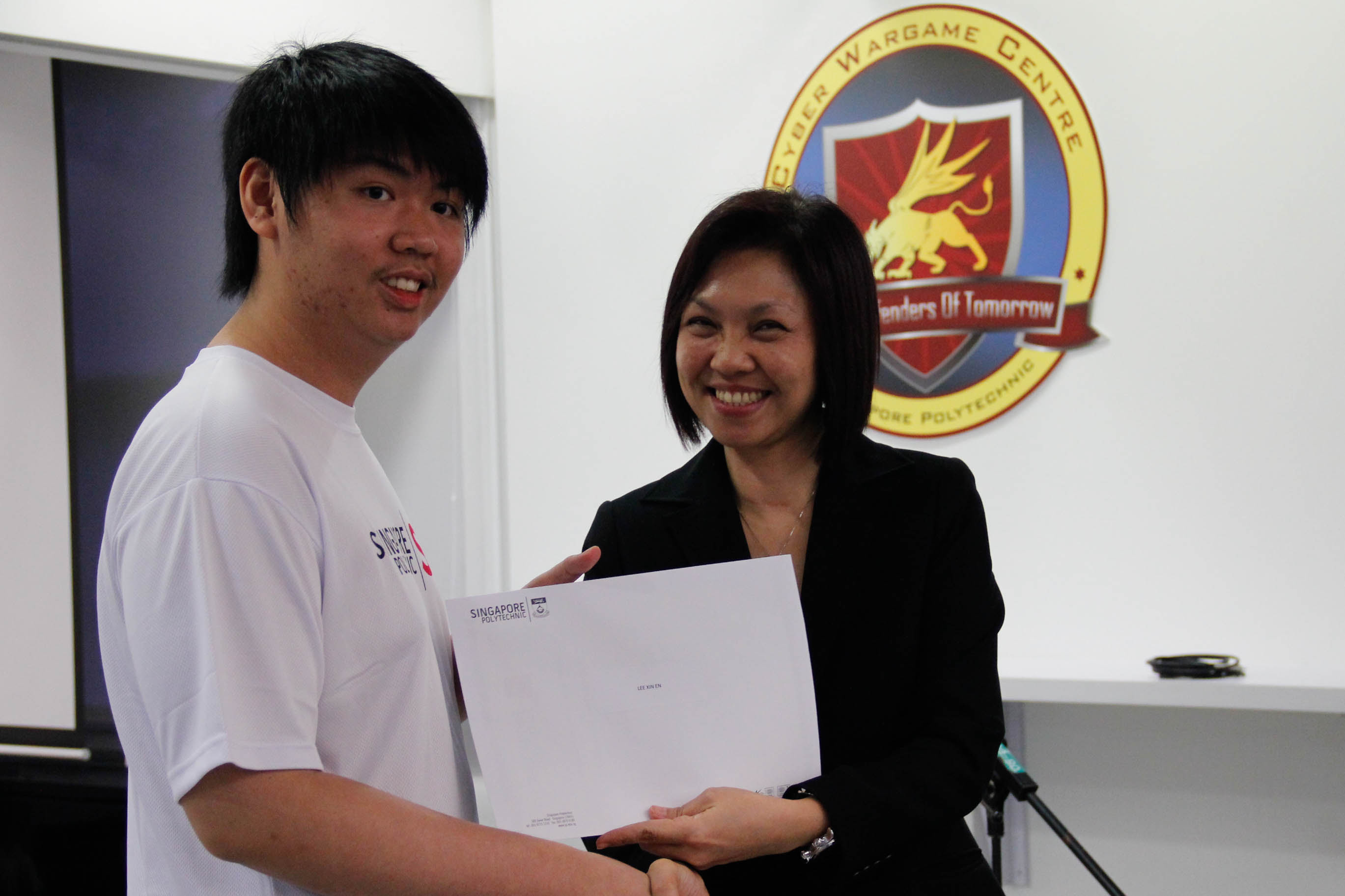 DMIT Director Ms Georgina Phua presenting Certificate of Participation in DISM CTF S1 to year 3 student Lee Xin En