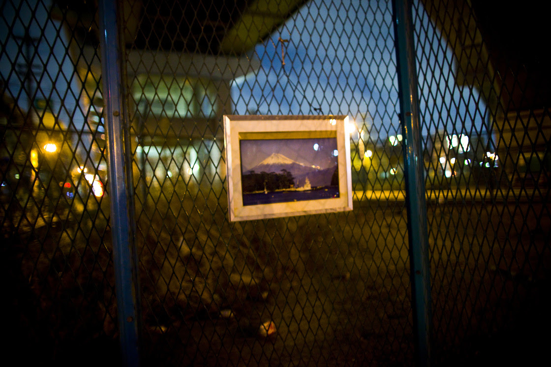 A picture of Mount Fuji hangs under a highway where a homeless man sleeps in Osaka, Japan.