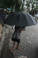 the umbrella selling boy-when i told him i will post his pictures in the papers he covered his face by firoze shakir photographerno1