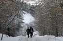 A couple walks on a snow covered road near the Lake of Eymir, Ankara, Turkey, on Sunday, Jan. 29, 2012. Winter temperatures and recent snowfall has partially paralyzed life in Turkey. (AP Photo/Selcan Hacaoglu)