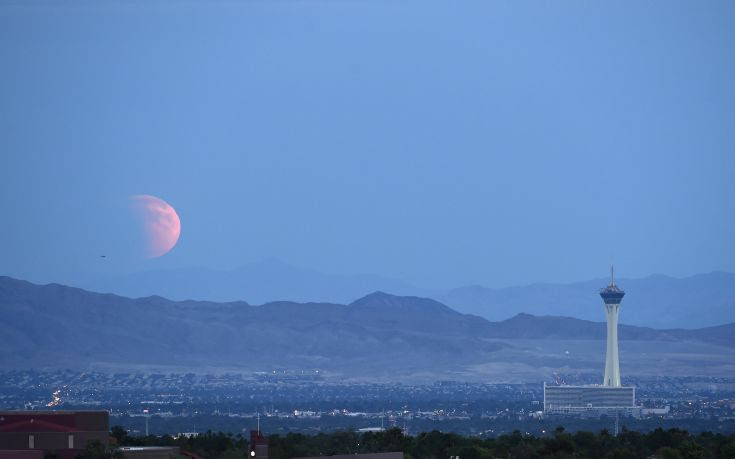 A partially eclipsed supermoon, the last of this year's supermoons, rises over Las Vegas, Nevada