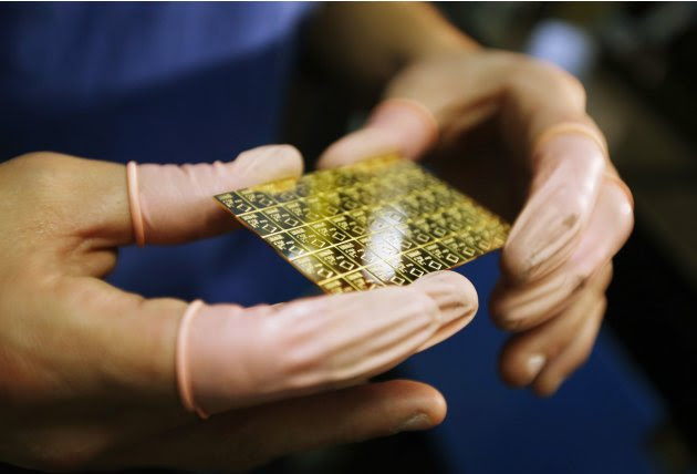 An employee checks a gold Combibar at a plant of gold refiner and bar manufacturer Valcambi SA in the southern Swiss town of Balerna
