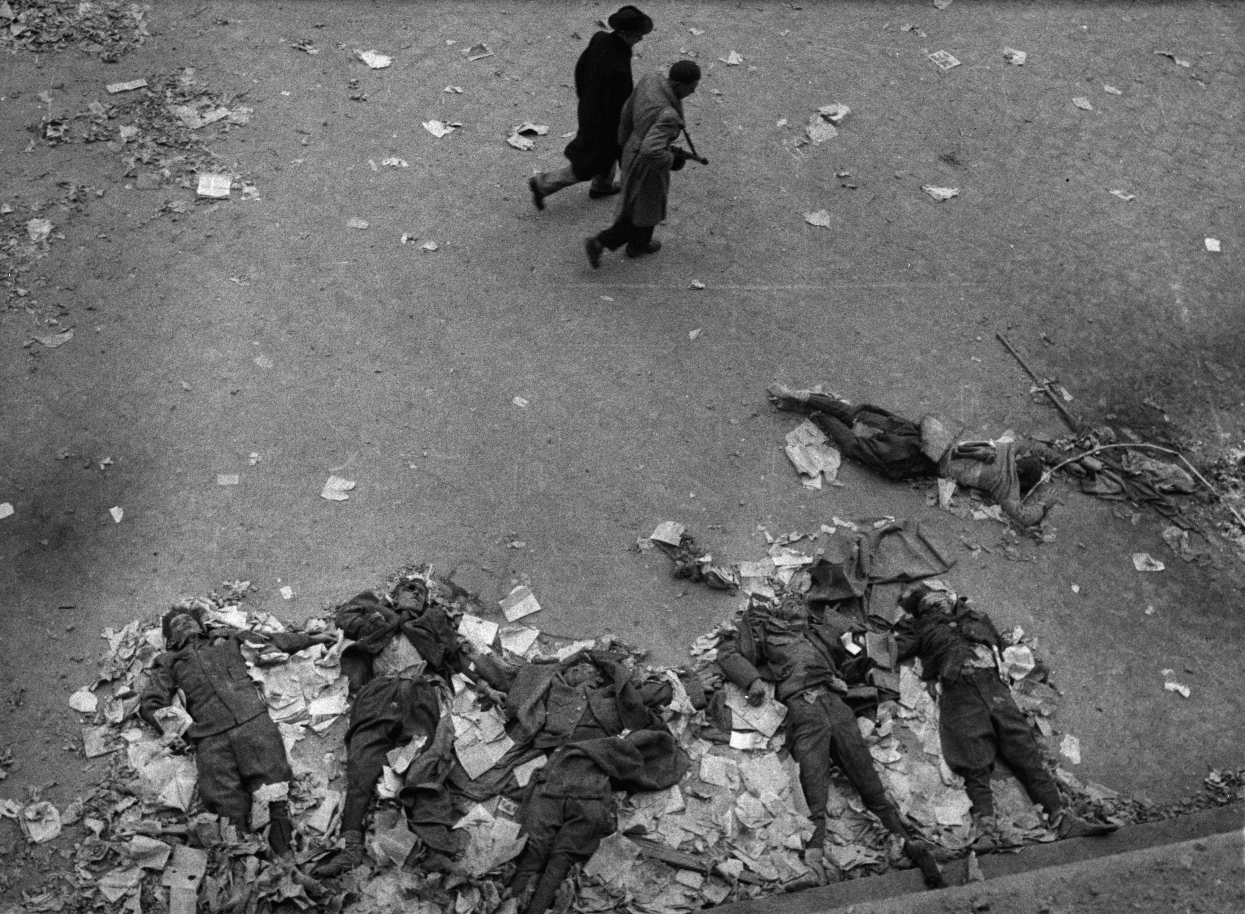 Two Hungarian revolutionaries walk past the bodies of Soviet secret policemen killed during the Hungarian Revolution, 1956.