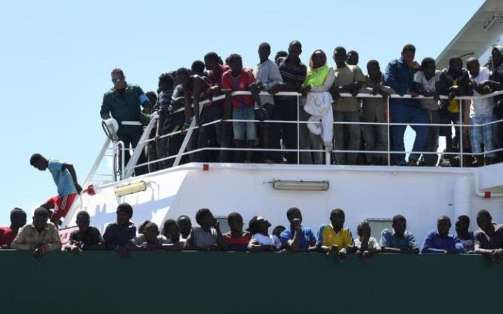 Migrants wait to disembark in the harbor of Salerno, Italy