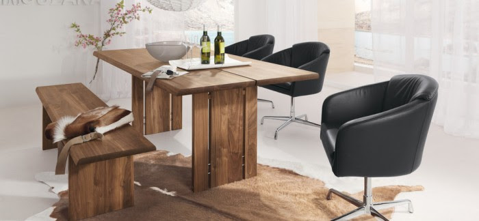 Both rustic and contemporary elements of distressed, warm-toned woods and sleek leather and chrome are used to create a modern decor that is incredibly appealing.  This is a dining room where you could spend hours lingering over a delicious meal with family and friends.