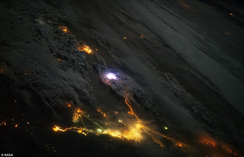 Shocking: The image, taken from the ISS, shows a white flash of lightning amid the yellow city lights of Kuwait and Saudi Arabia.Researchers are now using instruments onboard the space station to try and find out more about lightning and its effects