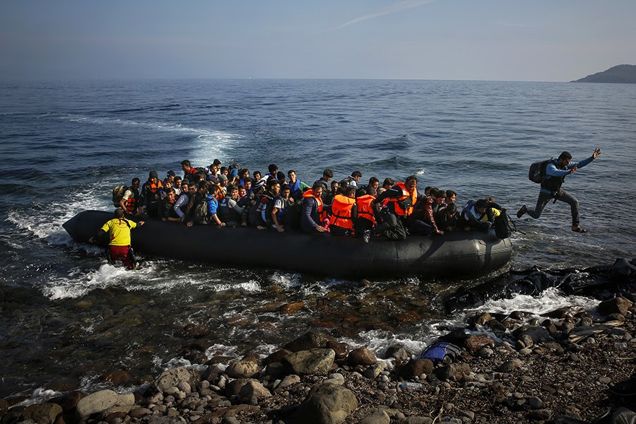 An Afghan migrant jumps off an overcrowded raft onto a beach at the Greek island of Lesbos (Yannis Behrakis, Thomson Reuters - October 19, 2015).
