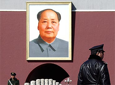 A policeman and paramilitary man stand guard in front of a giant portrait of the late Chairman Mao Zedong at Tiananmen Square in Beijing, China