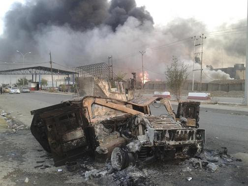 A burnt vehicle is seen during clashes between Iraqi security forces and al Qaeda-linked Islamic State in Iraq and the Levant (ISIL) in the northern Iraq city of Mosul, June 10, 2014. REUTERS-Stringer
