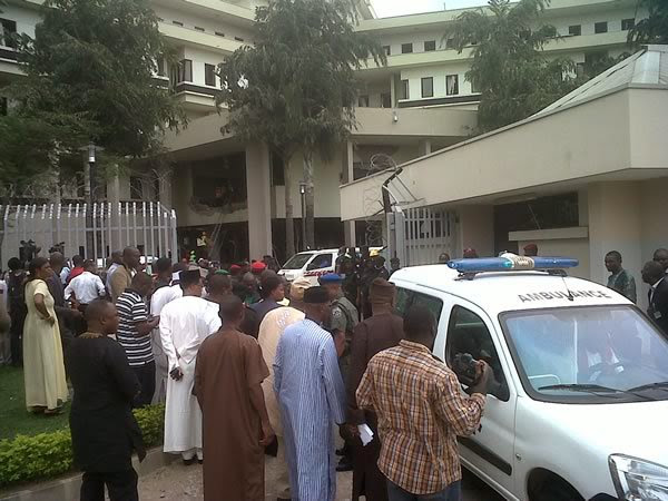 This image released by Saharareporters shows ambulances and rescue workers after a large explosion struck the United Nations' main office, background, in Nigeria's capital Abuja Friday Aug. 26, 2011,
