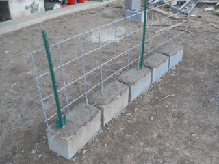 Pig fence piece concreted in cinder blocks