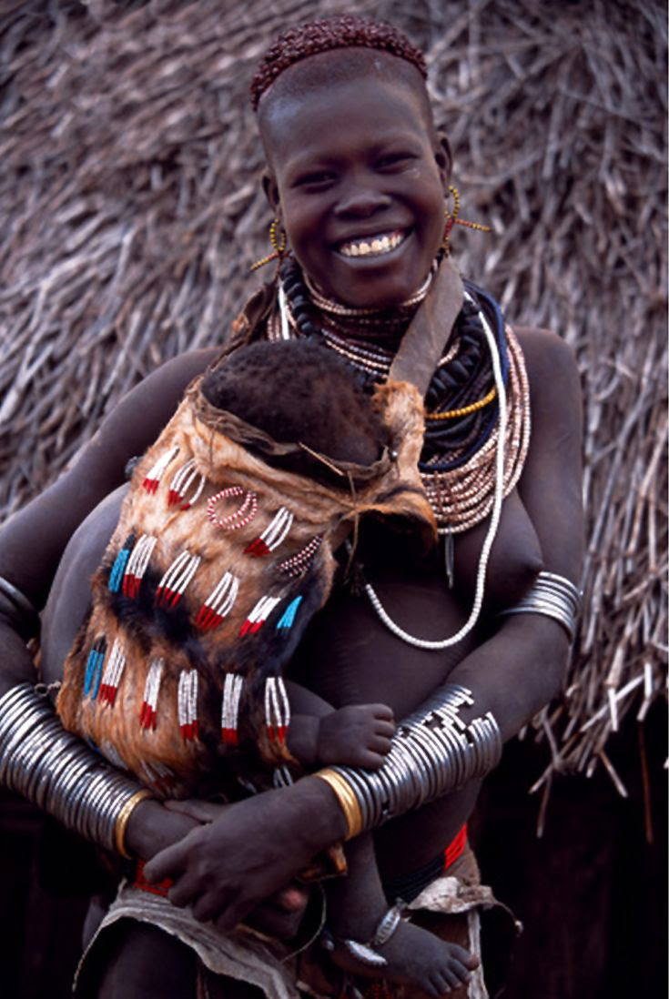 Africa | A young Nyangatom woman carries her baby on her hip in an elaborately braided papoose. Her hair has been reddened with a mixture of ochre and animal fat.  Typical of her tribe, she wears a calfskin skirt, multiple layers of bead necklaces and metal bracelets and amulets. Omo Valley, Ethiopia | ©John Warburton-Lee