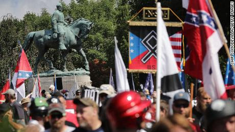 """A statue of Confederate General Robert E. Lee stands behind a crowd of white nationalists, neo-Nazis and members of the """"alt-right"""" movement during the """"Unite the Right"""" rally on August 12, 2017, in Charlottesville, Virginia. After clashes with counterprotesters and police, the rally was declared an unlawful gathering and protesters were forced out of Lee Park, home to the controversial statue."""