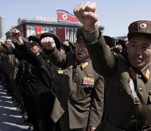 Oficiais do exército da Coreia do Norte dão socos no ar durante um comício na praça Kim Il Sung, no centro de Pyongyang. Dezenas de milhares de cidadãos compareceram ao local  (Foto: AP Photo/Jon Chol Jin)