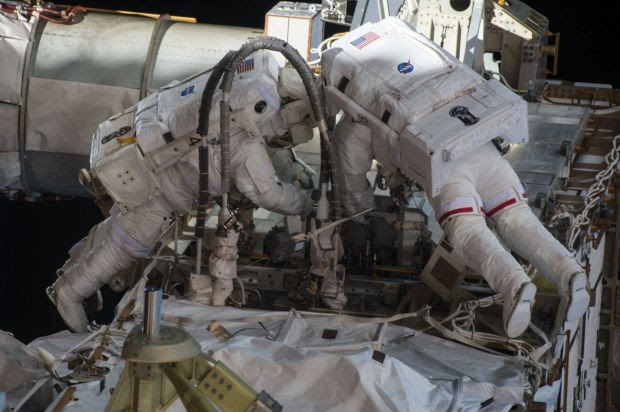 Scott Kelly (at left) undertaking a dangerous space walk outside the International Space Station