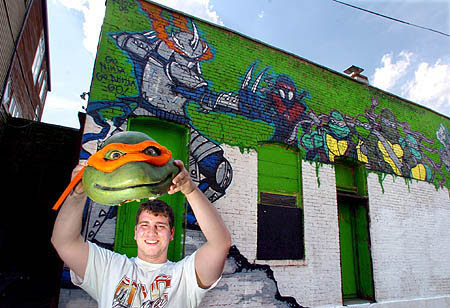Milton Barr, 20, shows a homemade mutant turtle mask used at his South Side movie and game rental store.
