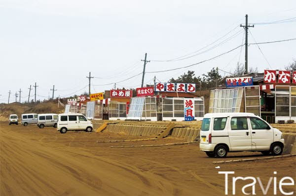 해변을 따라 포장마차들이 즐비하게 늘어서 있고 차들이 모래사장에 주차되어 있다