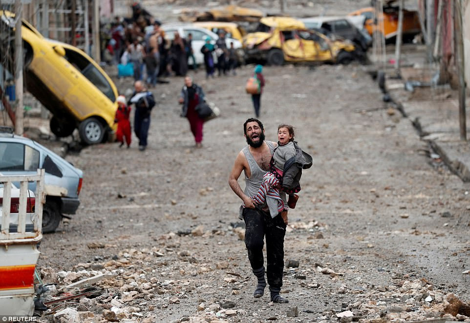 A crying man carries his daughter away from a part of Mosul in Iraq controlled by terrorist group Islamic State. The father is pictured fleeing from the Islamists toward Iraqi special forces soldiers during a battle on March 4