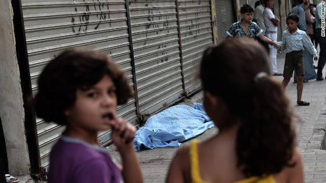 Children pass a bagged body outside a hospital in Aleppo on Thursday, August 30.