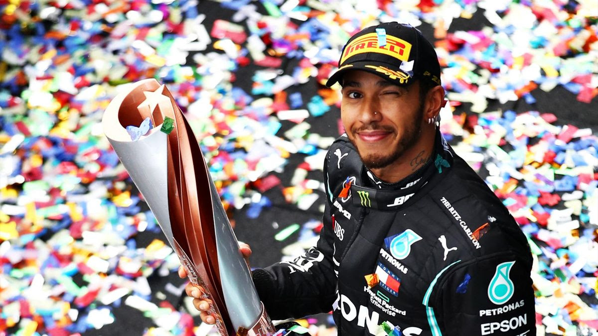 Race winner Lewis Hamilton of Great Britain and Mercedes GP celebrates winning a 7th F1 World Drivers Championship as he walks onto the podium, applauded by third placed Sebastian Vettel of Germany and Ferrari during the F1 Grand Prix of Turkey