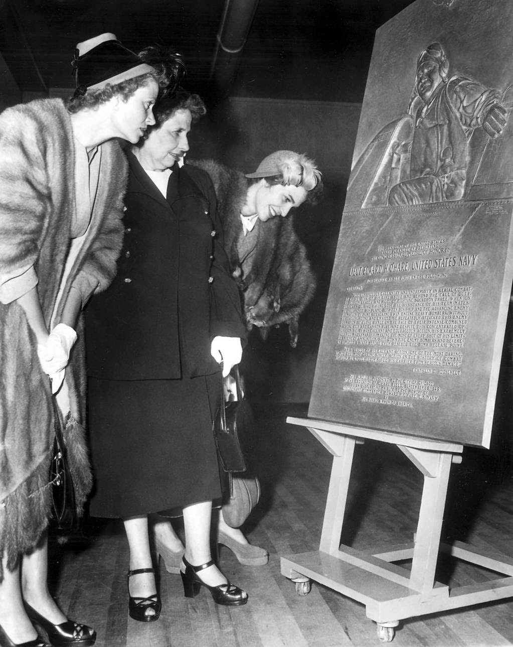 Mrs. Selma O'Hare, middle, and her daughters Mrs. Walter Palmer, left, and Mrs. Philip Tovrea, right, read the inscription on the bronze plaque commemorating the heroism of their son and brother Edward