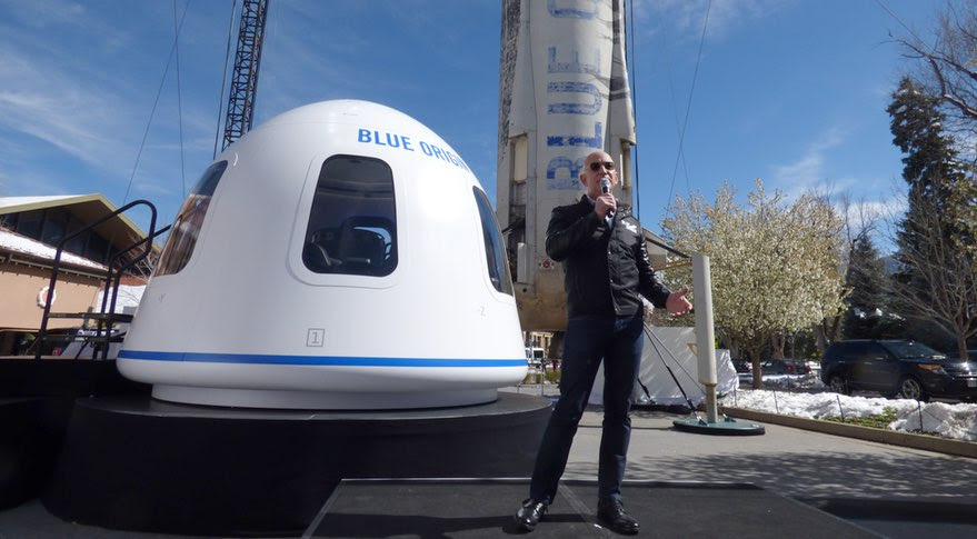 Blue Origin founder Jeff Bezos discusses the status of the company's New Shepard suborbital vehicle April 5 at the 33rd Space Symposium in Colorado Springs. Behind Bezos are a model of the New Shepard crew capsule and the propulsion module that flew five suborbital flights. Credit: SpaceNews/Jeff Foust