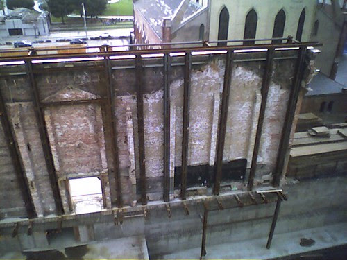 A brick wall being saved to be used as part of a new building