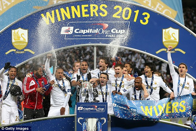 Historic: Captain Ashley Williams and his team-mates celebrate winning Swansea's first major trophy