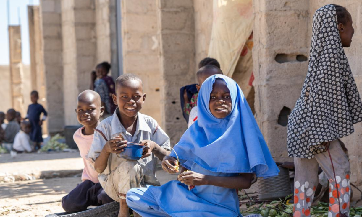 After finishing class in primary school, a girl (in blue uniform) plays with other children who are not in school, before going home, Kaleri, Borno State, Nigeria, 2019. The area, located near Jere, has been attacked several times by Boko Haram