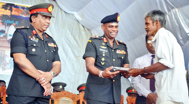 Army Commander Lieutenant General Mahesh Senanayake presenting an IDP with legal documents pertaining to the ownership of a house.