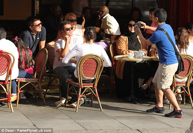 Simon Cowell is the centre of attention after opting for a seat at an outdoor table, in full view of the street
