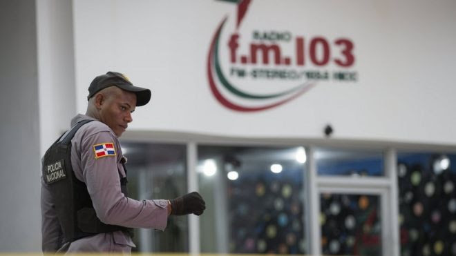 A Dominican policeman guarding the FM 103.5 radio station after the murders