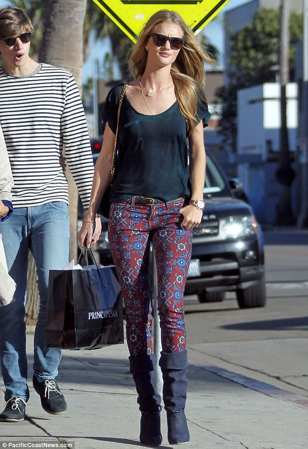 Stylish star: Rosie Huntington-Whiteley spends her day off shopping with pals while wearing a sheer black T-shirt and printed trousers