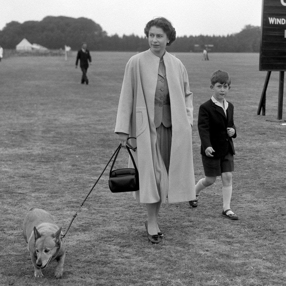 Queen Elizabeth II walking through Windsor Great Park with Prince Charles to watch the Duke of Edinburgh play polo