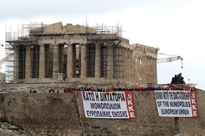 Miembros del Partido Comunista Griego despliegan dos pancartas en la Acrópolis de Atenas. -
